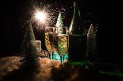 Eve Новые Годы предпосылки торжества с парами каннелюр и бутылки шампанского с рождественской елкой на снеге на темной предпосылк Стоковое Изображение