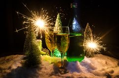 Eve Новые Годы предпосылки торжества с парами каннелюр и бутылки шампанского с рождественской елкой на снеге на темной предпосылк Стоковые Фото