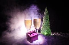 Eve Новые Годы предпосылки торжества с парами каннелюр и бутылки шампанского с рождественской елкой на снеге на темной предпосылк Стоковое Изображение RF
