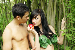 Eve and Adam. Biblical scene, Eve offers Adam the apple stock photography
