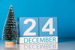 Eve Christmas 24 de diciembre Día 24 del mes de diciembre, calendario con poco árbol de navidad en fondo azul Invierno Fotos de archivo libres de regalías
