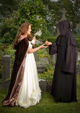 Eve and monk. Halloween scene of an evil monk offering an apple to a victorian woman Stock Image