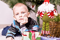 On the eve of New Year. The boy lies under a fir-tree with gifts Stock Photography