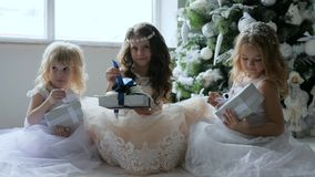 Eve New Year, children with gifts sit in chic dresses on floor near Christmas tree with ornaments. Eve New Year, children with gifts sit in chic dresses on floor stock footage