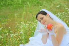 Eves temptation (bride portrait). Gorgeous bride tempting me with the forbidden fruit Stock Images