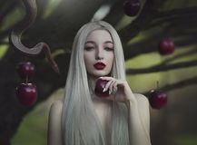 Eve with the serpent the tempter and the apple of sin. Young beautiful nude girl with very long white hair with a snake under the stock images