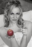 Eve of Temptation. A beautiful woman wrapped in sheets holding an apple and choosing...you Royalty Free Stock Images