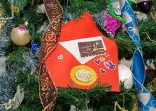 Evelope rouge avec des salutations de Saint Valentin et des mots écrits et étiquettes sur le fond d'arbre de Noël Image libre de droits