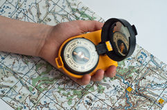 Compass on the map holding a child's hand. Stock Photos