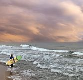 Female surfer on the beach at the sunset with stormy sea and surfboard. Even in the cold and stormy winter months, there are brave surfers like this woman, who Stock Photography