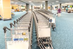 Even rows of luggage trolleys in the airport building. Even rows of empty trolleys for luggage in the building of a modern airport, people and people silhouettes stock images
