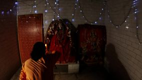 Evening aarti near statue of hindu Goddess Durga monk in orange clothes rings bell and repeats movements with burning light fixtur