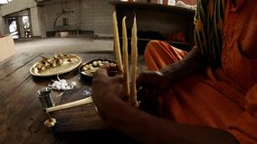 Hands tie big cotton wicks to light fixture Indian monk in orange clothes ritual accessories in metal plates