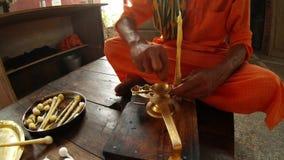 Hands tie big cotton wick in ghee to ritual light fixture Indian monk in orange clothes