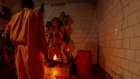 Aarti Hindu religious ritual of worship monk in orange clothes with light in hand in front of statue of Hanuman monkey God automat