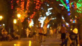 Evening alley with trees decorated with lights. In the alley walking people. Video is out of focus, people's faces are not visible stock video