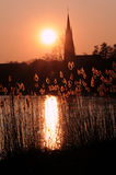 Evening ambience. Little town behind a lake in sunset Stock Photos
