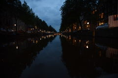 Evening on an Amsterdam canal with lit bridges at the enc. A look down an Amsterdam canal during an evening cruise with streetlights lining the canal and Stock Photos
