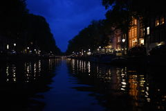 Evening on an Amsterdam canal with the reflections of the streetlights and buildings. A look down an Amsterdam canal during an evening cruise under a cobalt sky Stock Photo