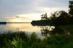 Calm, golden yellow sunset clouds on Cayuga Lake. Evening approaches on calm, quiet waters of Cayuga Lake in southern Finger Lakes of NYS Stock Image