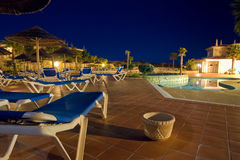 Evening Around Resort Pool. A late night shot of a deserted resort pool, with lounging chairs, and umbrellas Stock Photos