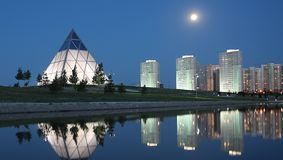 Evening in Astana Kazakhstan. Full moon rising over Astana Kazakhstan landmark and residential buildings Royalty Free Stock Photos