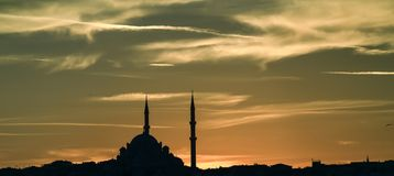 Evening atmosphere with dramatic sky over the dome and minarets of a mosque. royalty free stock photography