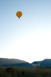 Evening Balloons. Yellow hot air balloon floating far above mountains in evening Royalty Free Stock Photo