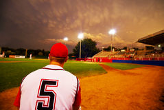 Evening baseball. Relief pitcher watching his team play baseball at night Stock Image