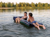 The evening bathing. Wet children playing on air bed on the river Stock Photography