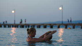 Evening bathing in sea of mother and son stock footage