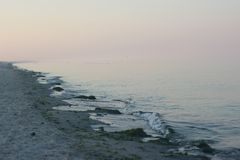 Gently pink sky smoothly passing into the blue sea. Coast. Waves. Evening beach on the Black Sea on the Kinburn Spit in Ukraine Royalty Free Stock Images