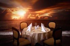 Evening beach dinner serving in sunset light Stock Images