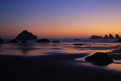 Evening beach horse ride. Three horseback riders riding at sunset on the beach under the moon Royalty Free Stock Images