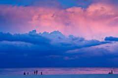 Evening Beach Scene. A beach scene in the evening at sunset. There are people on the beach with a dramatic stormy sky overhead. The last rays of sunlight are Royalty Free Stock Photo