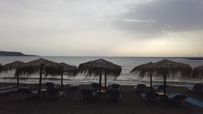 Evening on the beach with umbrellas and lounge chairs, wind and waves stock video footage