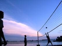 Evening beach volleyball. Area is in Sentosa Island, Singapore. The sunset was colourful and these men were having a game of volleyball. Picture was taken to Stock Photos