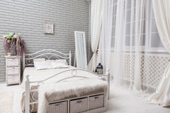 Evening bedroom with a white bed, big mirror near the window at Stock Image