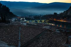 Evening in Berat. Evening Berat, town is the south of Albania, with its hills, covered with mist, illuminated Gorica Bridge over Osum river and old buildings Stock Photography