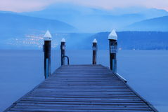 Evening blue dock on the lake. Looking down the dock and across the lake, smoke in the hills Royalty Free Stock Photo