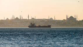 Evening on the Bosporus. A cargo ship against the background of the Sultan Ahmed district stock images