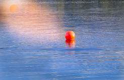 In the evening. The buoy is reflected in the sunset light in the lake Royalty Free Stock Images
