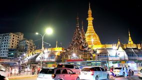 Evening in busy Yangon, Myanmar. YANGON, MYANMAR - FEBRUARY 14, 2018: The heavy traffic at the bright golden stupa of Sule Pagoda, located in Downtown, on stock footage