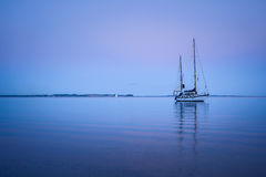 Evening calm, Aarhus Bay, Denmark. A two-masted yacht lies on the calm waters of Aarhus Bay, Denmark, with only a few ripples in the perfect mirror of the royalty free stock photography