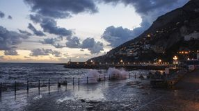 Evening in Campania, Almalfi. Evening breeze crash waves into the town harbour of Almalfi Royalty Free Stock Photography