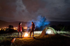 Evening camping. Man and woman standing by the campfire Royalty Free Stock Image