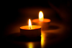 Evening by candlelight. Two candles are lit one after the other in the dark on the table Stock Photo