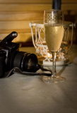 Evening with champagne. Camera on a table near glass with champagne Stock Images