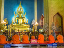 Evening chant in Marble temple. BANGKOK - APRIL 16: Monk come together in hall of main church of Marble temple for evening chant front of The main Buddha statue Stock Photography