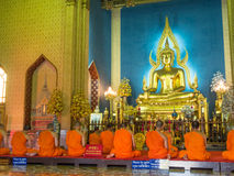 Evening chant in Marble temple. BANGKOK - APRIL 16: Monk come together in hall of main church of Marble temple for evening chant front of The main Buddha statue Royalty Free Stock Photography